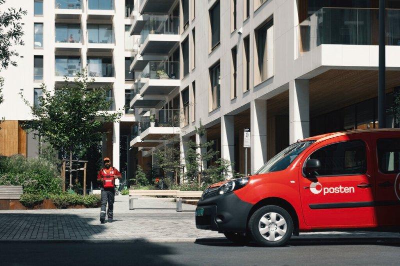 Postbud og bil i urbane omgivelser.